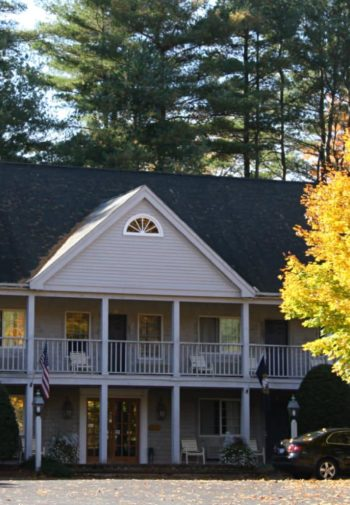 Jack Daniels Motor Inn - Sided two-story building with steep roof, two-story porches surrounded by tall beautiful trees