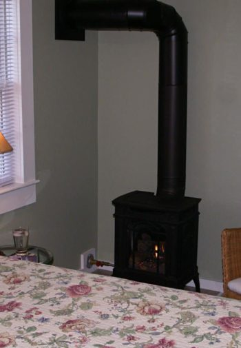 Guest room with floral bedding, fire stove, wicker chair and window