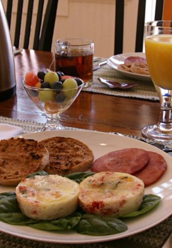 Table set for breakfast - eggs, English muffins, Canadian bacon, fresh fruit, coffee, and juice