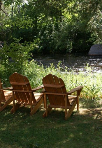 Four wood Adirondack chairs in the grass between trees overlooking a bubble river