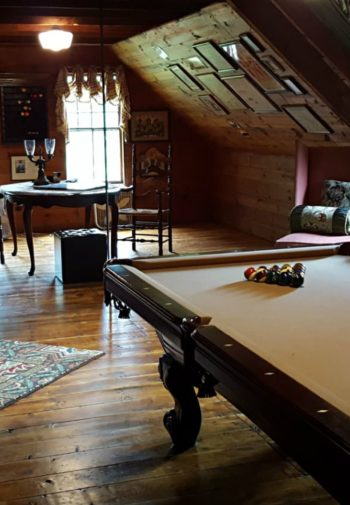 Cozy wood paneled room with slanted ceiling, wood floors, pool table, chairs and tables