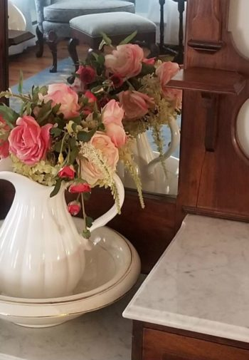 Antique vanity table with mirror, marble top, wash basin and pitcher filled with flowers, and oil lamp