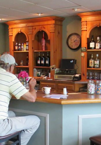 Golf club bar room with counter and stools, beverages and TV