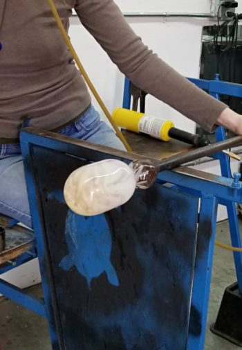 Woman demonstrating how to create blown glass