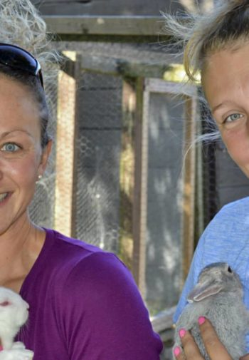 Two smiling women holding gray and white bunnies outside farm pens