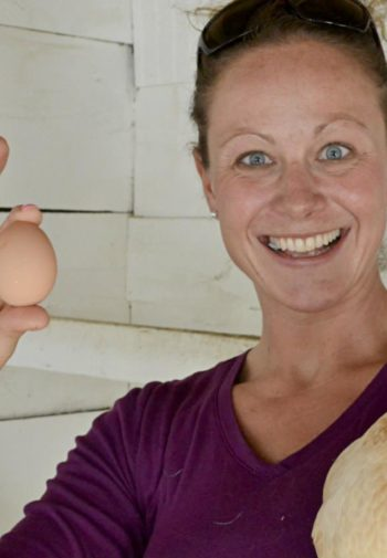 Smiling woman holding a chicken and a brown egg