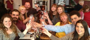 Group of people smiling and clinking their wine glasses