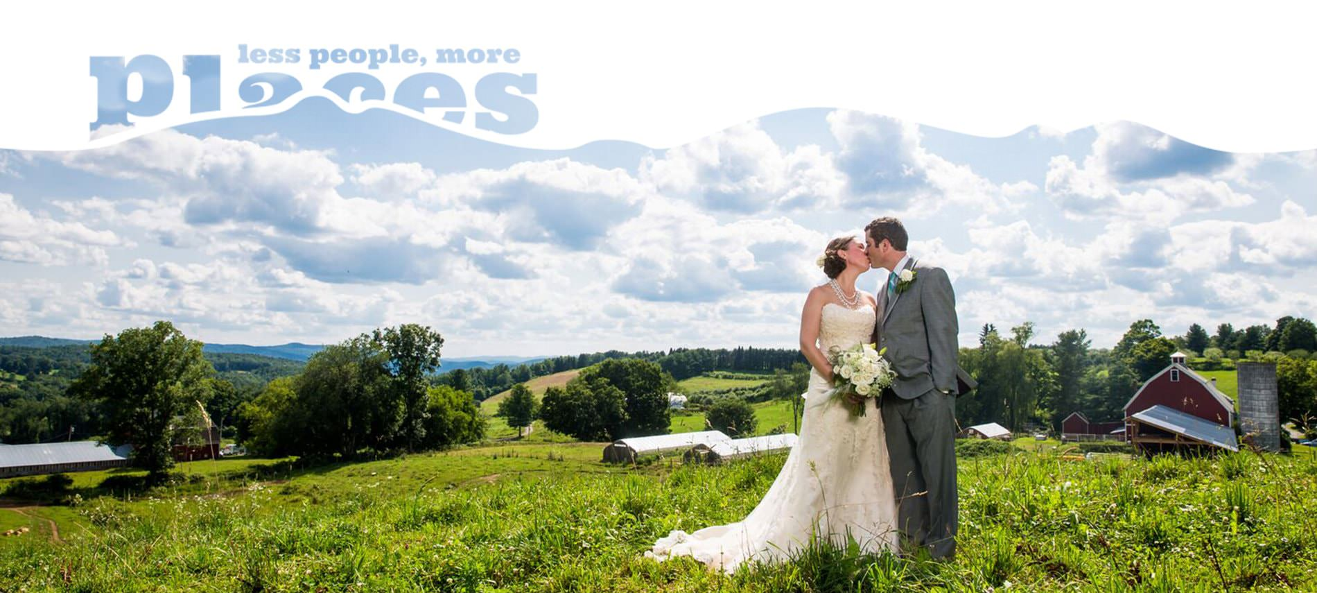 Bride and groom kissing in a grassy field surrounded by trees and blue skies with puffy clouds