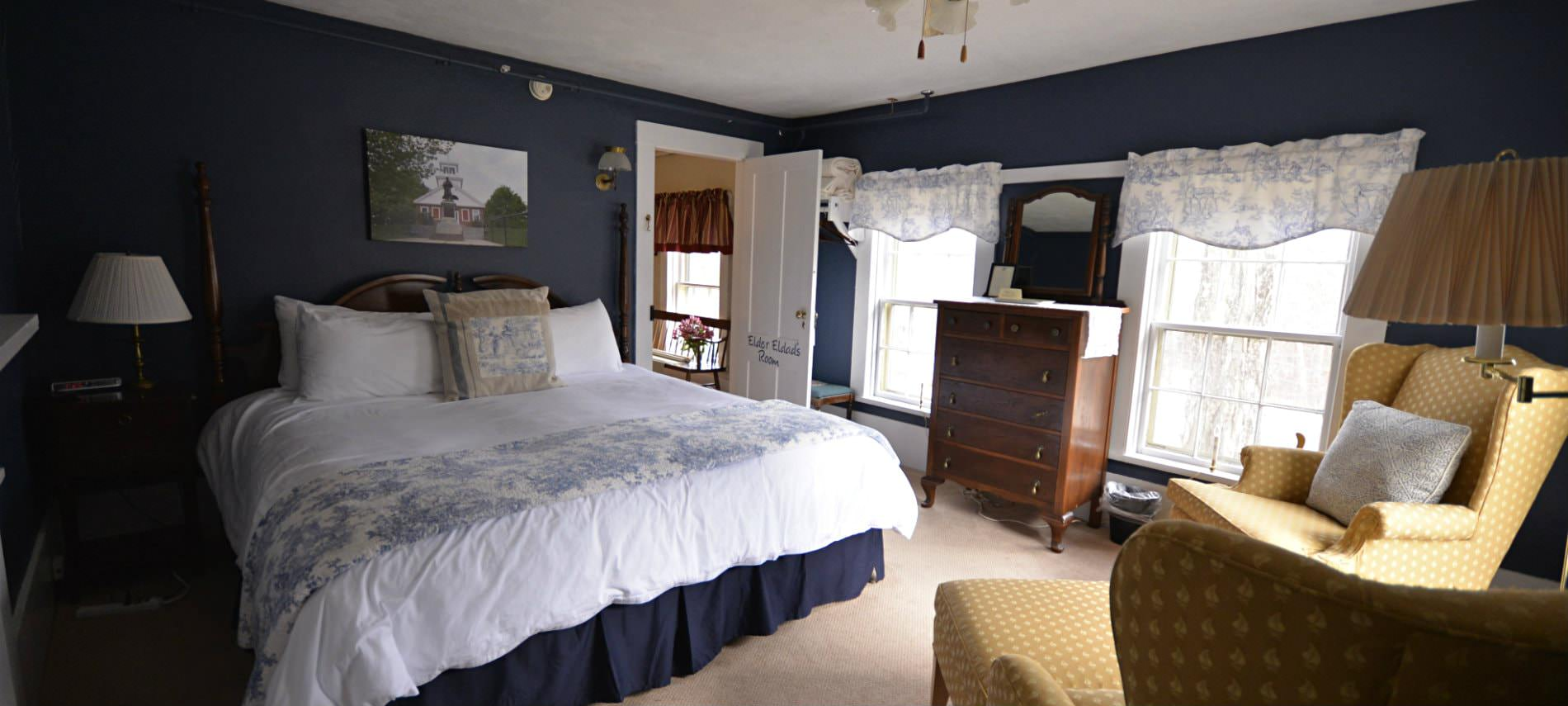 Spacious navy guest room, bed with white bedding, yellow upholstered wingback chairs, carpet, dresser and two windows