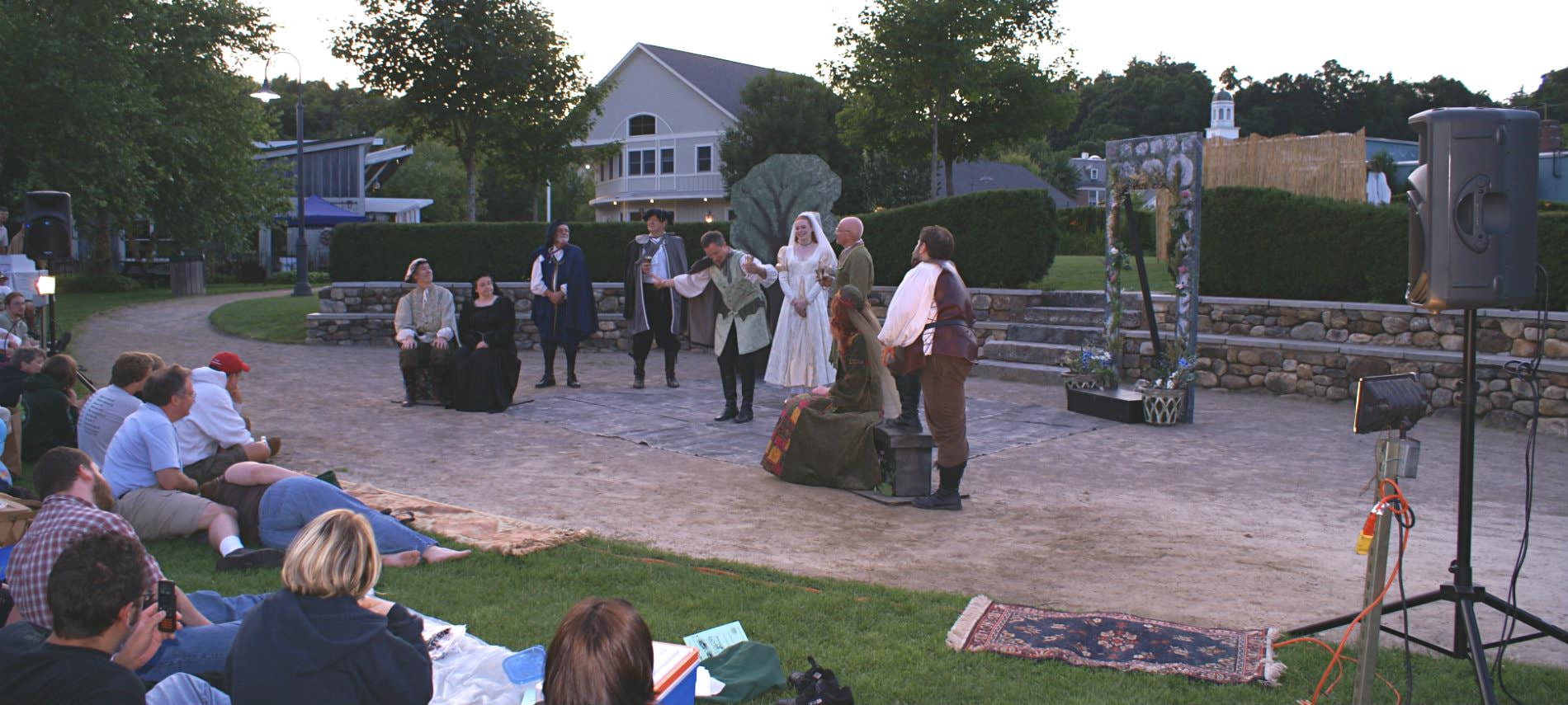 Costumed entertainers on a large patio performing for an audience