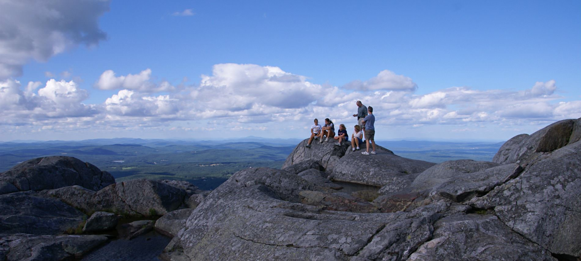 Group of people sitting on a rock ledge overlooking miles of tree covered hills