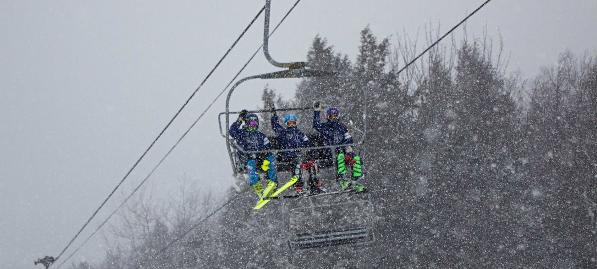 Three people in ski lift waving with snow falling