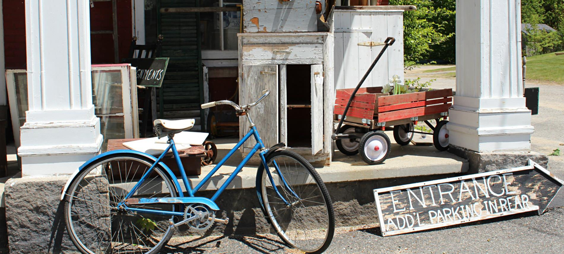 Entrance to antique store with blue bicycle and red wagon