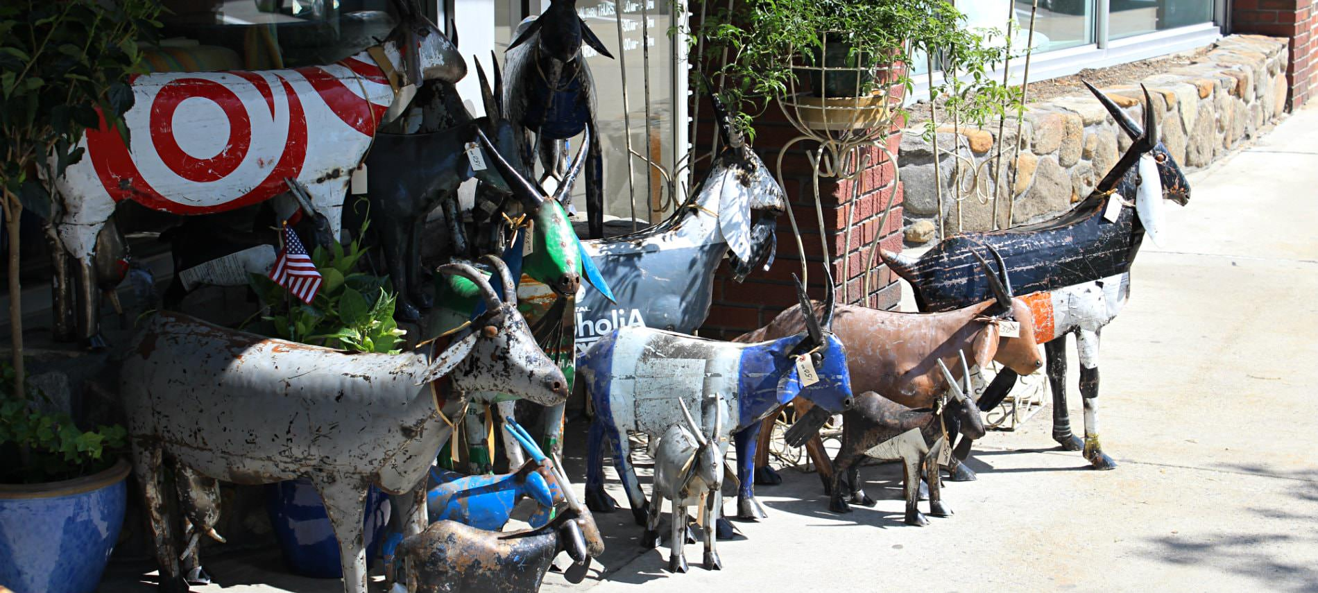 handcrafted metal goats in different colors outside a shop