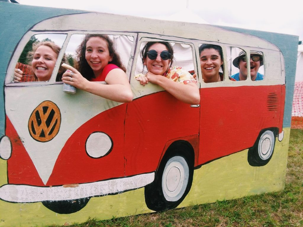 Five smiling concert attendees pretend to drive a VW bus painted on a sign board.